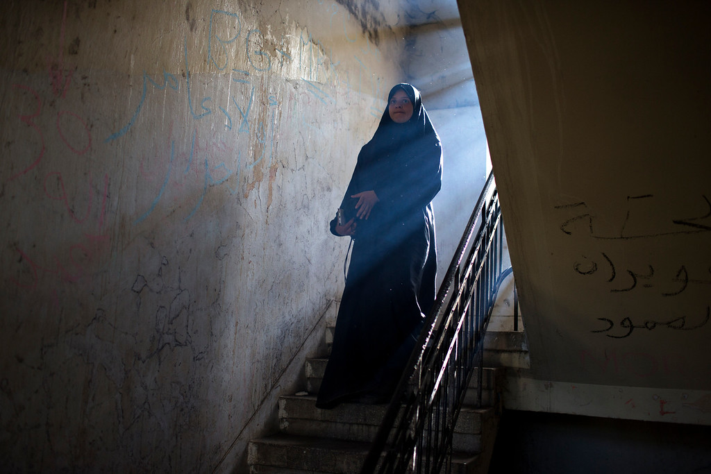 . A woman walk downstairs in an abandoned building where refugees and migrants are living at a makeshift refugee camp at the northern Greek border point of Idomeni, Greece, on Saturday, May 14, 2016. Thousands of stranded refugees and migrants are camped at the makeshift refugee camp of the northern Greek border point of Idomeni. (AP Photo/Petros Giannakouris)