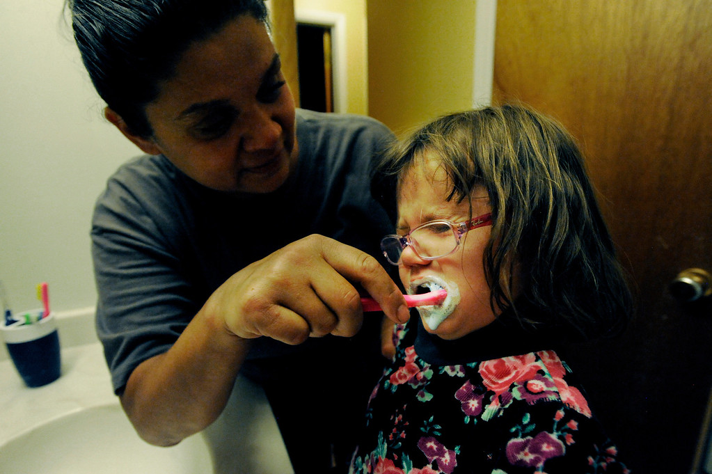 . Ena, left, helps her 4-year-old, Olivia, brush her teeth before bed. Ena and Brent Batron are both blind, and raising their five kids under the age of 10.  Photo by Jamie Cotten, Special to The Denver Post