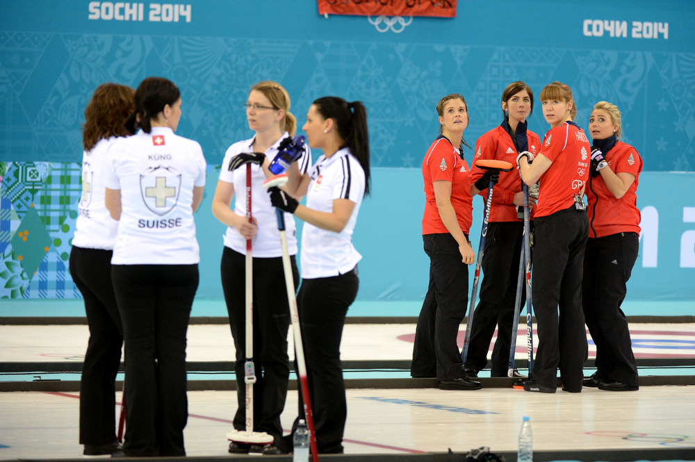 . Switzerland (L) and Great Britain (R) teams discuss strategy during the Women\'s Curling Bronze Medal Game at the Ice Cube Curling Center during the Sochi Winter Olympics on February 20, 2014.  DAMIEN MEYER/AFP/Getty Images