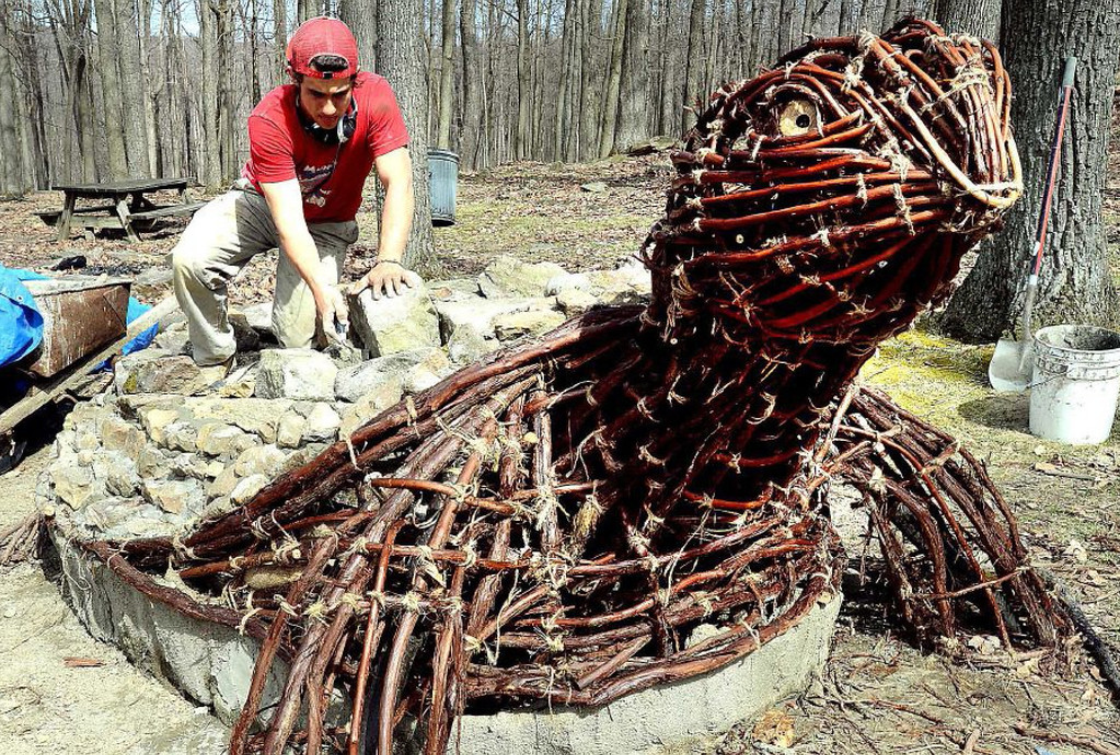 . In this photo taken on Monday, April 21, 2014, West Virginia University senior art student Ben Gazsi works on his Earth Day sculpture of a turtle made from twisted grape vines and stones for the shell at Coopers Rock State Park in Bruceton Mills, W.Va. (AP Photo/The Dominion Post, Ron Rittenhouse)