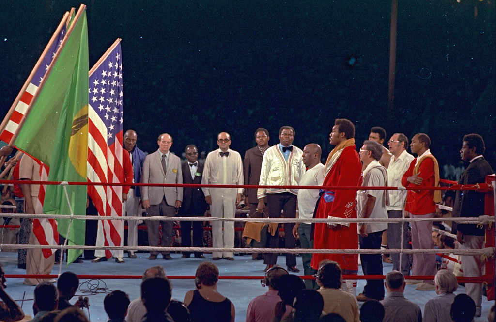 . The opening ceremony of the national anthem is shown in Kinshasa Stadium, Zaire, Africa, October 30, 1974, prior to the world heavyweight championship bout between George Foreman and challenger Muhammad Ali.  George Foreman is alongside the ropes in a red robe.  Ali is fourth from the right, partially obscured.  (AP Photo)