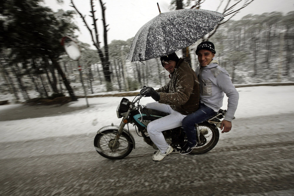 Description of . A man rides his motorbike as snow falls in the village of Nabeh al-Safa, Lebanon on January 8, 2013. Stormy weather, including high winds and heavy rainfall, lashed the eastern Mediterranean coast, downing power lines and trees and causing several injuries in a number of countries. JOSEPH EID/AFP/Getty Images