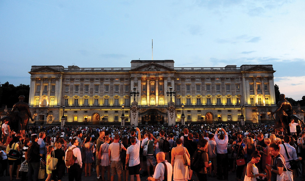 . Members of the public celebrate outside Buckingham Palace after an easel was placed in the forecourt of the Palace with the notification to announce the birth of a baby boy, at 4.24pm to the Duke and Duchess of Cambridge at St Mary\'s Hospital in west London, Monday July 22, 2013.(AP Photo/Clive Gee, PA)