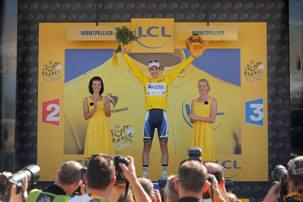 . Daryl Impey of South Africa, wearing the overall leader\'s yellow jersey, celebrates on the podium of the sixth stage of the Tour de France cycling race over 176.5 kilometers (110.3 miles) with start in Aix-en-Provence and finish in Montpellier, southern France, Thursday July 4, 2013. (AP Photo/Laurent Cipriani)