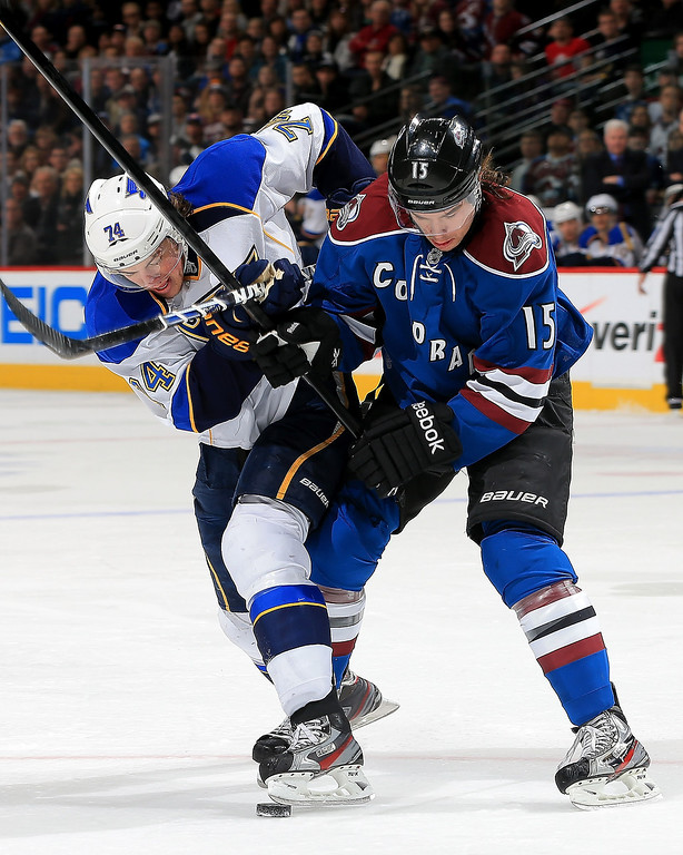 . T.J. Oshie #74 of the St. Louis Blues and P.A. Parenteau #15 of the Colorado Avalanche battle for control of the puck in the first period at the Pepsi Center on February 20, 2013 in Denver, Colorado.  (Photo by Doug Pensinger/Getty Images)