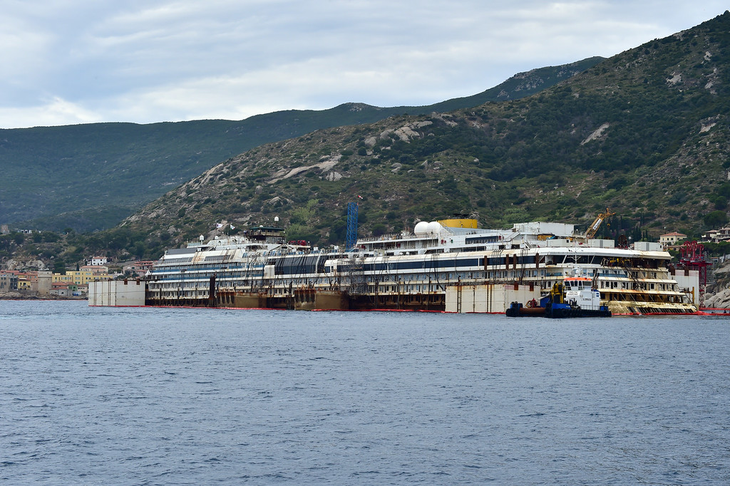 . A picture shows the wreck of the Costa Concordia cruise ship starting being lifted out of water during an operation to refloat the boat on July 14, 2014 off the Giglio Island. Over two and a half years after it crashed off the island of Giglio in a nighttime disaster which left 32 people dead, the plan is to raise and tow away the 114,500-tonne vessel in an unprecedented and delicate operation for its final journey to the shipyard where it was built in the port of Genoa.            (GIUSEPPE CACACE/AFP/Getty Images)