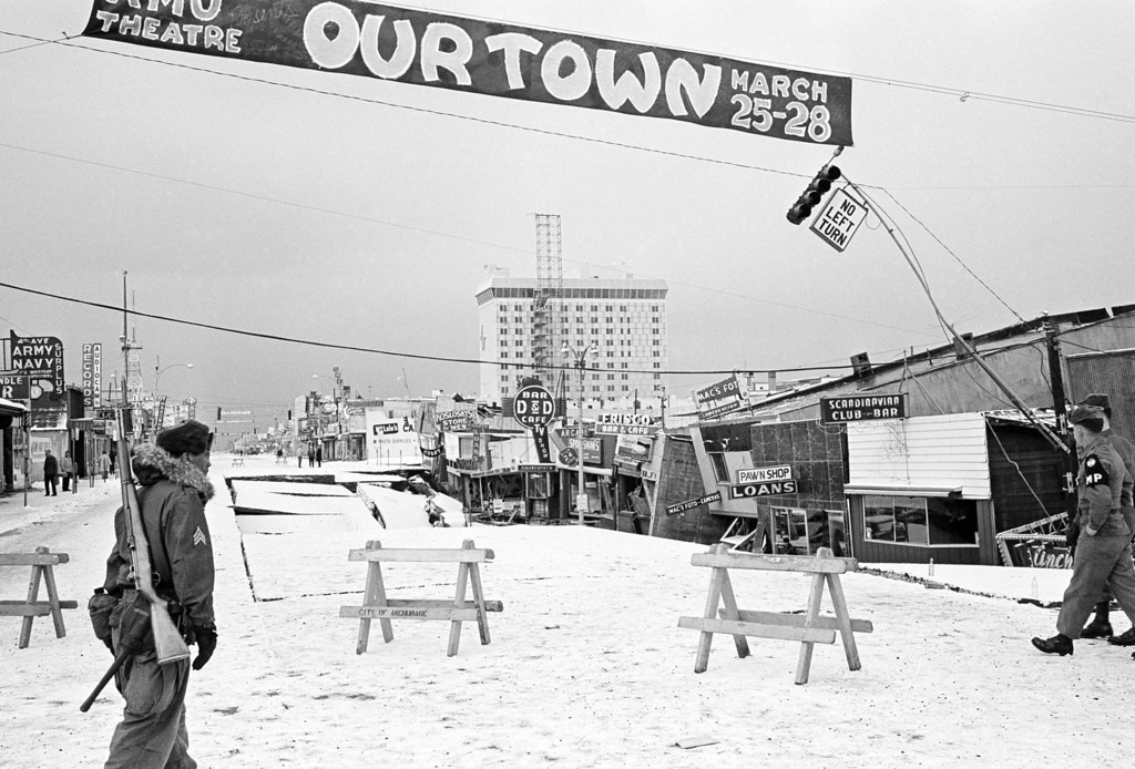 . In this March 29, 1964 file photo, a soldier crosses Fourth Avenue, the main street in Anchorage, Alaska, a city under martial law following the devastation visited upon it by an earthquake.  The sign overhead advertises a production of the Thornton Wilder play.  Buildings at right were called a total loss.  (AP Photo/File)