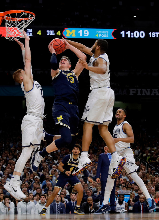 . Michigan forward Moritz Wagner, center, drives to the basket between Villanova defenders Donte DiVincenzo, left, and Omari Spellman, right, during the first half in the championship game of the Final Four NCAA college basketball tournament, Monday, April 2, 2018, in San Antonio. (AP Photo/David J. Phillip)