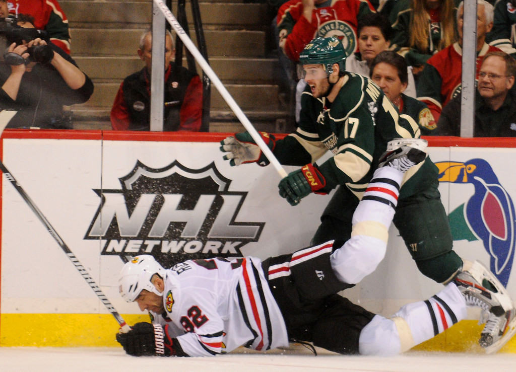 . Minnesota left wing Torrey Mitchell, right, checks Chicago defenseman Michal Rozsival to the ice in the third period. (Pioneer Press: John Autey)