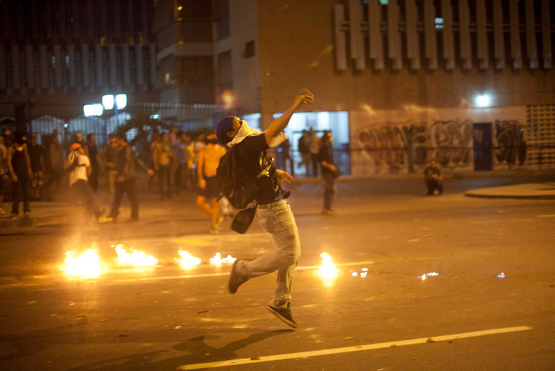 . A demonstrator throws a fire bomb during clashes with National Guard as they protest against the official results of last Sunday\'s presidential elections in downtown Caracas, Venezuela, Monday, April 15, 2013. National Guard troops fired tear gas and plastic bullets to disperse demonstrators protesting the official results in Venezuela\'s disputed presidential election.   (AP Photo/Ramon Espinosa)