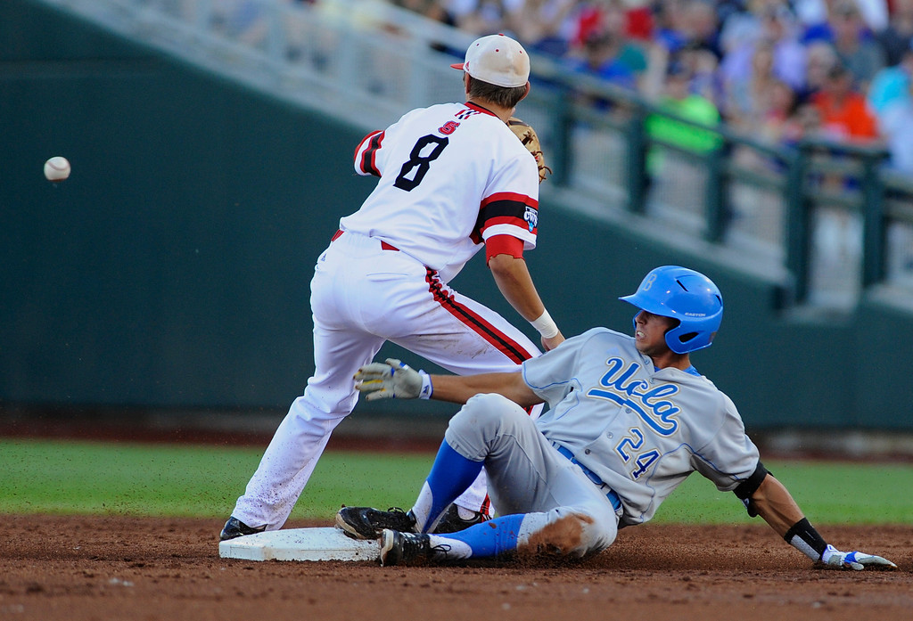 . UCLA\'s Brian Carroll reaches second base ahead of the throw to North Carolina State shortstop Trea Turner after hitting a double in the second inning of an NCAA College World Series game in Omaha, Neb., Tuesday, June 18, 2013. (AP Photo/Eric Francis)