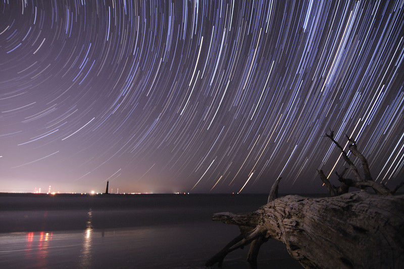 Star trails over a deadwood tree on the beach, with the silhouette of the Morris Island Lighthouse in the distance, on the northeast end of Folly Beach, SC on Friday, November 29, 2013. Copyright 2013 Jason Barnette  This is a one-hour star trail composed of 124 individual 30-second exposures. The heavy light pollution in the distance comes from Charleston (far left) and Sullivan's Island (right of lighthouse). The bright light and reflection in the water just to the left of the Morris Island Lighthouse is the still-functional Sullivan's Island Lighthouse.