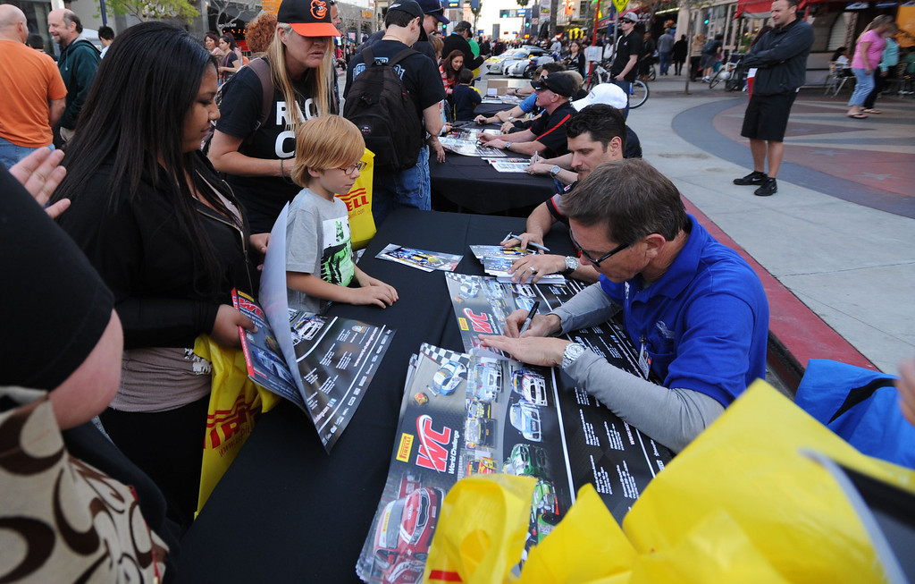 . Long Beach, Calif., -- 04-18-13- Race car drivers sign autographs as fans got a close-up look at race cars along Pine Ave. during the  Tecate Light Thunder Thursday On Pine.  Race fans were able to  meet drivers and see stuns motorcycles and IndyCar pit demonstrations.   Stephen Carr/  Los Angeles Newspaper Group