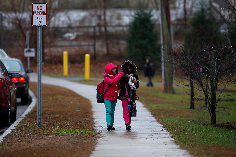 Description of . School children walk outside Ellsworth Avenue Elementary School after class was dismissed in Danbury, Connecticut December 17, 2012. Parents agonized over whether to send their kids to school and cautious educators locked down school districts near Newtown, Connecticut at the first hint of trouble on Monday, making for a nervous first day back to school since the massacre at Sandy Hook Elementary School in Newtown, Connecticut. REUTERS/Joshua Lott