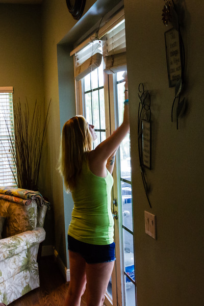 """Shelby Sparrow, 21, of Plantation, Florida, cleans the french doors that lead outside to the patio and pool enclosure at the All About Recovery younger women's sober home in Loxahatchee, Florida on Friday, June 24, 2016. Residents are required to keep the sober home clean, but once a week, the residents  are assigned an area of the sober house to """"deep clean"""". (Joseph Forzano / The Palm Beach Post)"""