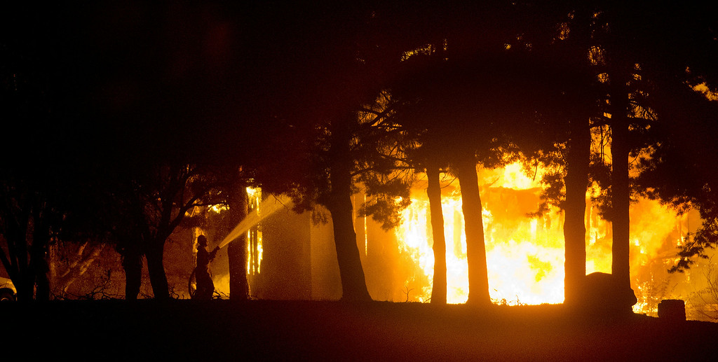 . A firefighter puts water on one of the structures burning in Pateros, Wash. on Thursday night, July 17, 2014, as fire sweeps through town. Many homes were lost in the blaze. (AP Photo/The Wenatchee World, Mike Bonnicksen)