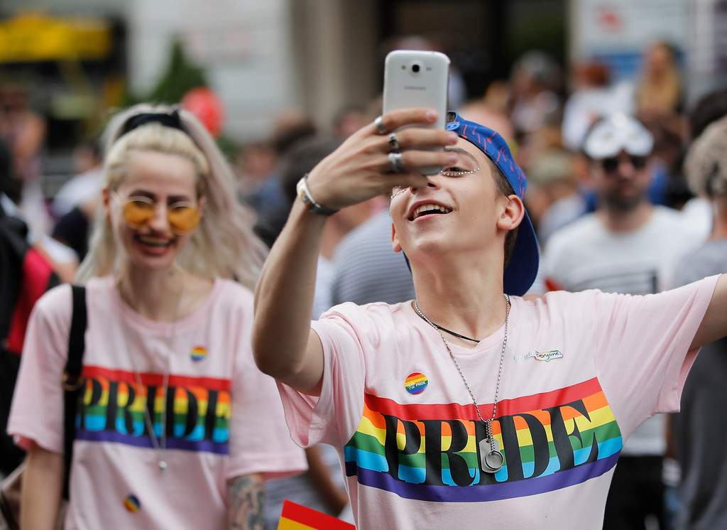 . Participant take pictures during the gay pride parade in Bucharest, Romania, Saturday, June 9, 2018. People taking part in the gay pride parade in the Romanian capital demanded more rights and acceptance for same-sex couples. (AP Photo/Vadim Ghirda)