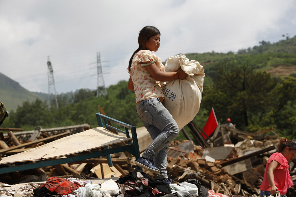 . A woman walks over the debris of collapsed houses following an earthquake at Longtoushan township of Ludian county in Zhaotong, southwest China\'s Yunnan province, on August 5, 2014.  AFP PHOTOSTR/AFP/Getty Images