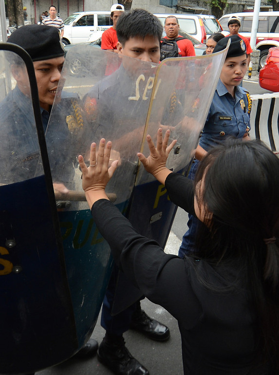 ". Members of Philippine women\'s group Gabriela are pushed back by police during a surprise rally near the gates of Malacanang palace in Manila on March 7, 2013, accusing President Benigno Aquino of mishandling the Sabah stand-off situation between followers of a self-styled Philippine sultan and Malaysian troops. Malaysia\'s defence minister on March 7 rejected a ceasefire offer by a self-styled Philippine sultan unless his fighters who launched a deadly incursion ""surrender unconditionally\"".   TED ALJIBE/AFP/Getty Images"