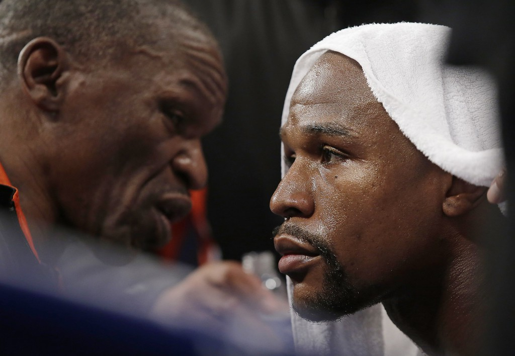 . Floyd Mayweather Jr., right, listens to his father, head trainer Floyd Mayweather Sr., between rounds during his welterweight title fight against Manny Pacquiao, from the Philippines, on Saturday, May 2, 2015 in Las Vegas. (AP Photo/Isaac Brekken)