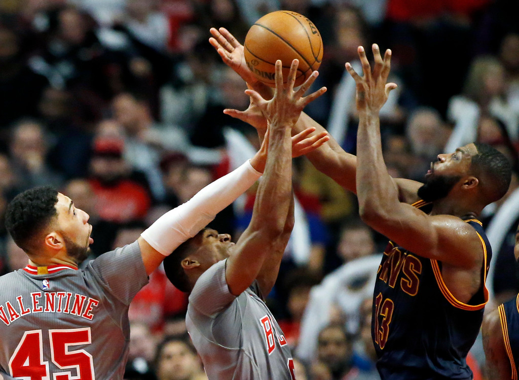 . Cleveland Cavaliers forward/center Tristan Thompson, right, battles for a rebound against Chicago Bulls guard Denzel Valentine, left, and guard Rajon Rondo during the second half of an NBA basketball game Thursday, March 30, 2017, in Chicago. The Bulls won 99-93. (AP Photo/Nam Y. Huh)