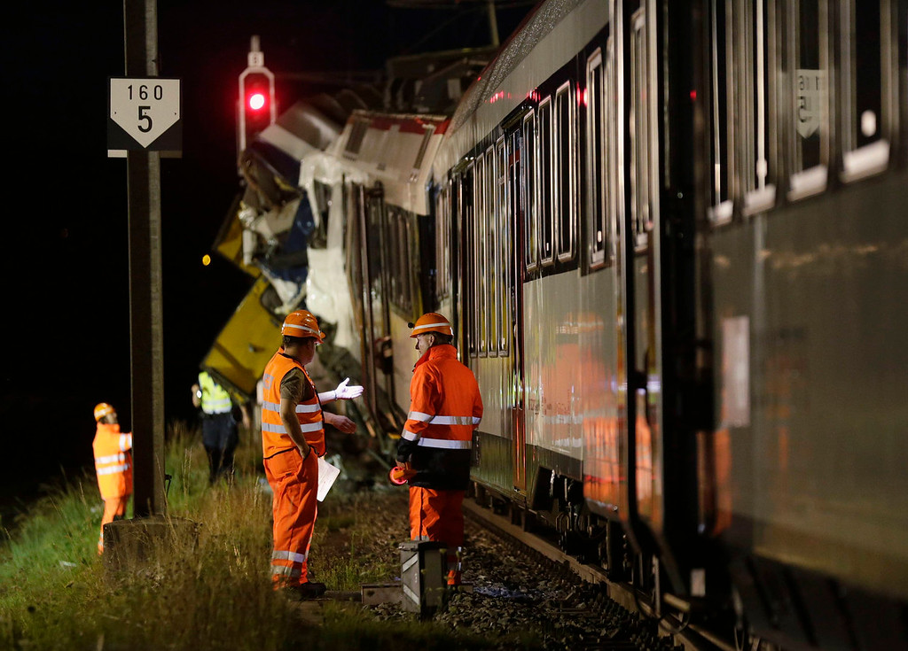 . Rescue workers are seen at the site of a head-on collision between two trains near Granges-pres-Marnand, near Payerne in western Switzerland July 29, 2013. Two trains collided head-on in Switzerland on Monday evening, injuring about 35 people, five seriously, police said. The driver of one of the trains was still unaccounted for and thought to be inside the wreckage, at Granges-pres-Marnand in the canton of Vaud, police spokesman Jean-Christophe Sauterel said. REUTERS/Denis Balibouse