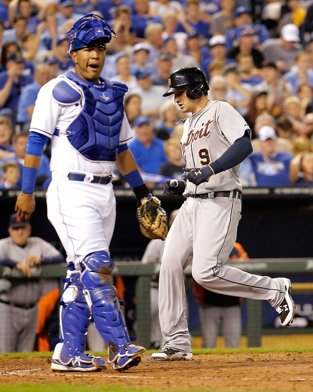 . Detroit Tigers\' Nick Castellanos (9) runs past Kansas City Royals catcher Salvador Perez to score on a throwing error by second baseman Omar Infante during the fifth inning of a baseball game Friday, Sept. 19, 2014, in Kansas City, Mo. (AP Photo/Charlie Riedel)