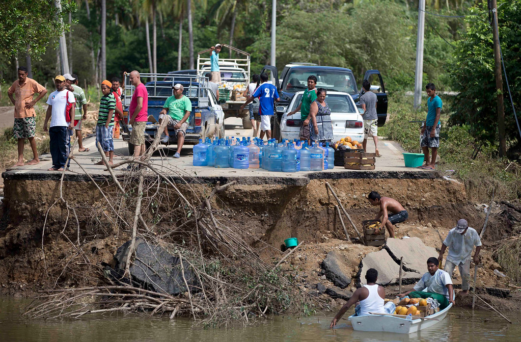 . People stand on the edge of a collapsed bridge as they wait to ferry their goods via a boat across the Papagayos River, south of Acapulco, near Lomas de Chapultepec, Mexico, Wednesday, Sept. 18, 2013. Mexico was hit by the one-two punch of twin storms over the weekend, and the storm that soaked Acapulco on Sunday - Manuel -re-formed into a tropical storm Wednesday, threatening to bring more flooding to the country\'s northern coast. With roads blocked by landslides, rockslides, floods and collapsed bridges, Acapulco was cut off from road transport.  (AP Photo/Eduardo Verdugo)