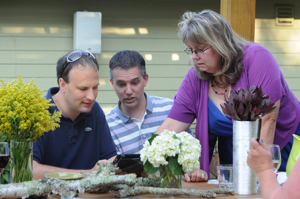 . Bradley Weber, left, and Ryan Pfeifle look over floral arrangements on an iPad at florist Carra Otten\'s La Petite Fleur floral shop on St. Paul\'s West Side with the help of wedding planner Julie Lyford of Fabulous Functions. The two decided to incorporate wedding vases from their commitment ceremony 10 years ago. ( Pioneer Press: Ginger Pinson)