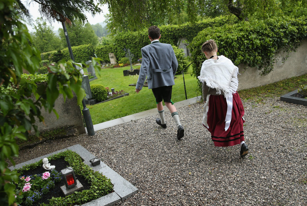 . A boy and girl wearing traditional Bavarian folk costumes depart after attending the annual Corpus Christi (in German called Fronleichnam) mass at St. Michael\'s Church on May 30, 2013 in Seehausen am Staffelsee, Germany. The Seehausen Corpus Christi celebration usually includes a procession to a chapel across the nearby Staffelsee lake, though rain forced organizers to cancel the lake procession this year. Corpus Christi is among the highlights of the Catholic religious calendar in Bavaria.  (Photo by Sean Gallup/Getty Images)
