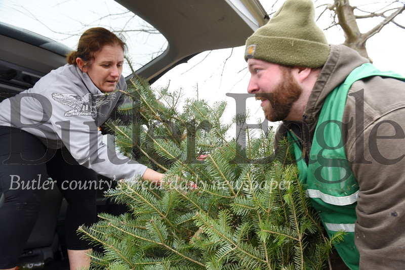 Harold Aughton/Butler Eagle: Wes Sherry of Cypher's Tree Farm, helps load a Christmas tree into the back of Penny Birch's minivan.
