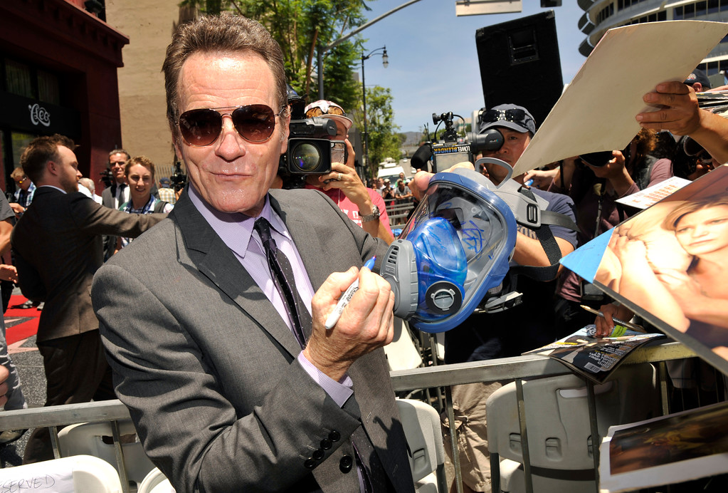 """. Actor Bryan Cranston, who plays high school chemistry teacher and methamphetamine manufacturer Walter White on the television series \""""Breaking Bad,\"""" signs a gas mask for a fan after receiving a star on the Hollywood Walk of Fame on Tuesday, July 16, 2013 in Los Angeles. (Photo by Chris Pizzello/Invision/AP)"""