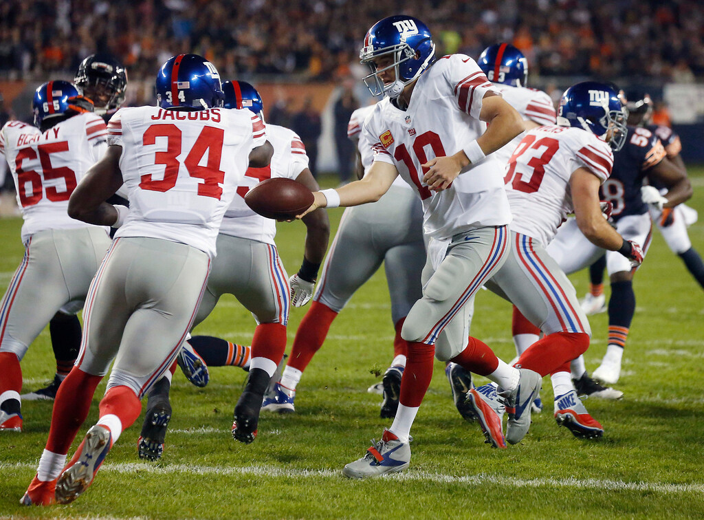 . New York Giants quarterback Eli Manning (10) hands off to running back Brandon Jacobs (34) in the first half of an NFL football game against the Chicago Bears, Thursday, Oct. 10, 2013, in Chicago. (AP Photo/Charles Rex Arbogast)
