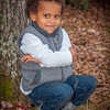 Young african-american boy sitting by a tree for his portrait smiling for the camera. He is hugging himself while sitting on the ground.