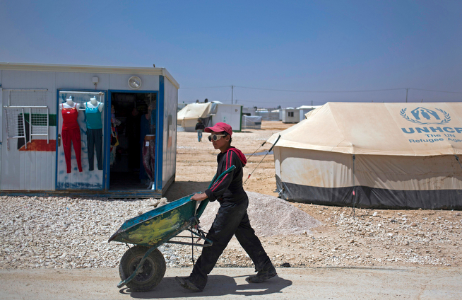 . In this Thursday April 17, 2014 photo, a Syrian boy wearing sunglasses passes by a caravan used as a clothing shop at Zaatari refugee camp, near the Syrian border in Jordan. Some residents, frustrated with Zaatari, the region\'s largest camp for Syrian refugees, set up new, informal camps on open lands, to escape tensions and get closer to possible job opportunities.(AP Photo/Khalil Hamra)