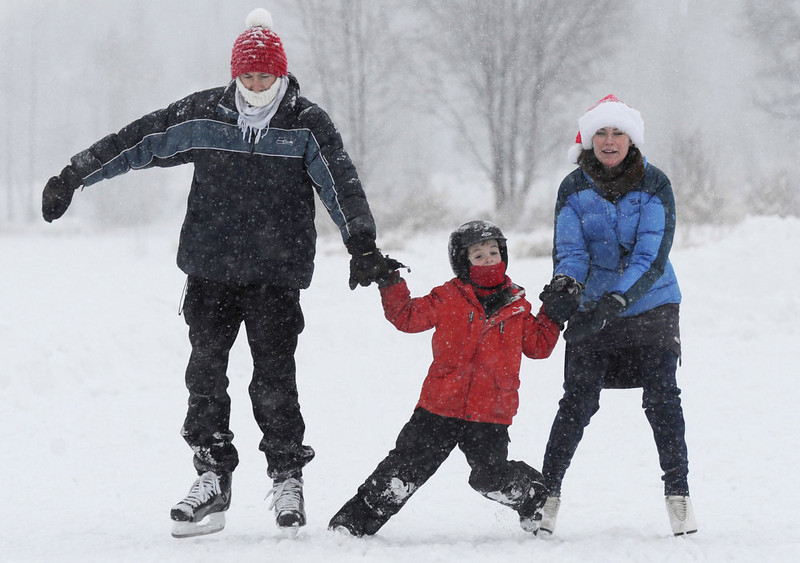 . Kris Jones and his wife Robin Grendahl hang on to their son Erik Jones, 7, while ice skating at Westchester Lagoon in Anchorage during a snowstorm on Christmas Day, Tuesday, Dec. 25, 2012. (AP Photo/Anchorage Daily News, Bill Roth)