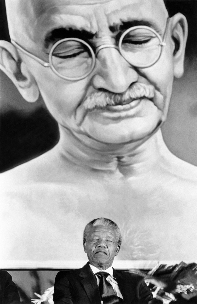 . Anti-apartheid leader and African National Congress (ANC) member Nelson Mandela appears to be in a similary meditative mood as Mahatma Gandhi depicted in painting at top on October 15, 1990 in New-Delhi where Mandela is on an official state visit. (FILM)  AFP PHOTO/P. MUSTAFA (Photo credit should read P. MUSTAFA/AFP/Getty Images)