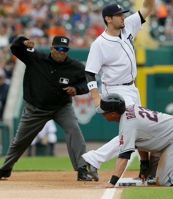 . Third base umpire Laz Diaz calls out Cleveland Indians\' Michael Brantley as Detroit Tigers third baseman Nick Castellanos raises his glove after the tag on an attempted steal during the first inning in the first baseball game of a doubleheader, Saturday, July 19, 2014 in Detroit. (AP Photo/Carlos Osorio)