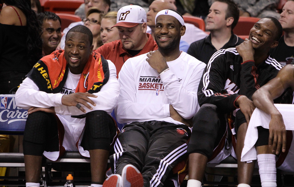 . Miami Heat guard Dwyane Wade, left, forward LeBron James, center, and  forward Chris Bosh, right, smile as they sit on the bench in the final minutes of the fourth quarter during an NBA basketball game against the Phoenix Suns in Miami Wednesday, Nov. 17, 2010. The Heat defeated the Suns 123-96. (AP Photo/Lynne Sladky)