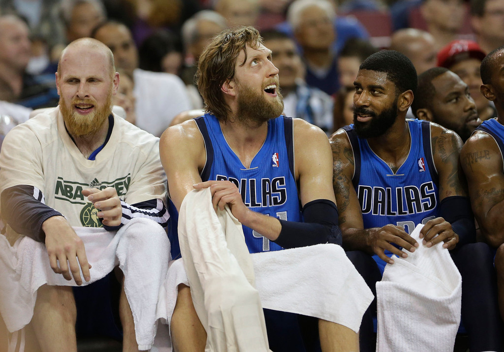 . Dallas Mavericks forward Dirk Nowitzki, of Germany, smiles as he looks up at the scoreboard while sitting with teammate Chris Kaman, left, and O.J. Mayo during the fourth quarter of an NBA basketball game against the Sacramento Kings in Sacramento, Calif., Friday, April 5, 2013.  The Mavericks won 117-108. (AP Photo/Rich Pedroncelli)