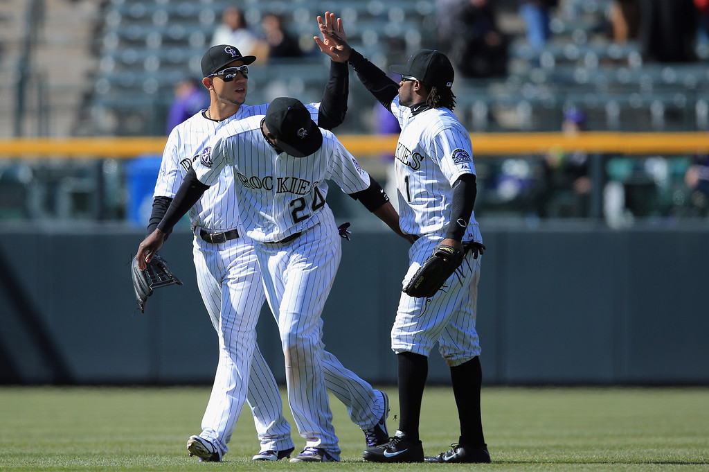 . Outfielders Carlos Gonzalez #5, Dexter Fowler #24  and Eric Young Jr. #1 of the Colorado Rockies celebrate their 11-3 victory over the New York Mets at Coors Field on April 18, 2013 in Denver, Colorado.  (Photo by Doug Pensinger/Getty Images)