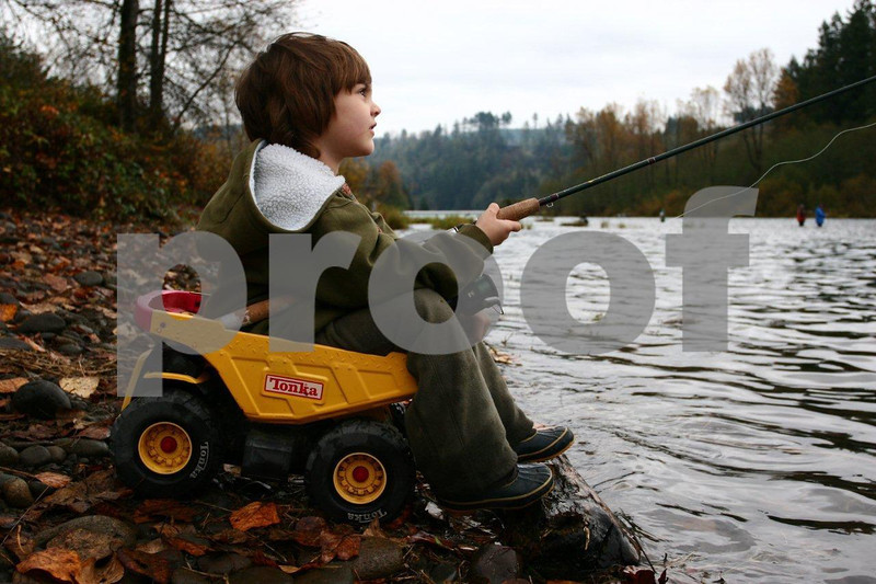 Boy sits in Tonka toy while fishing.
