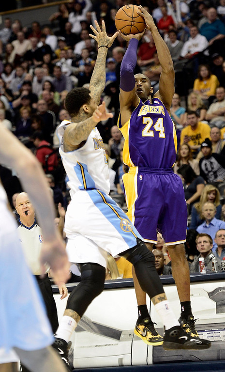 . Los Angeles Lakers Kobe Bryant (R) takes a shot over the reach of Denver Nuggets Wilson Chandler (L) during their NBA basketball game in Denver, Colorado February 25, 2013. REUTERS/Mark Leffingwell