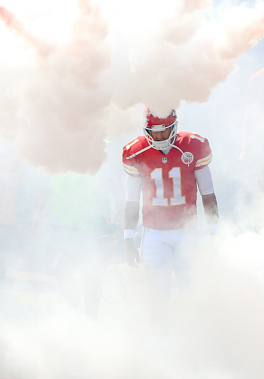 . KANSAS CITY, MO - SEPTEMBER 29:  Quarterback Alex Smith #11 of the Kansas City Chiefs runs through smoke while being introduced prior to the game against the New York Giants at Arrowhead Stadium on September 29, 2013 in Kansas City, Missouri.  (Photo by Jamie Squire/Getty Images)