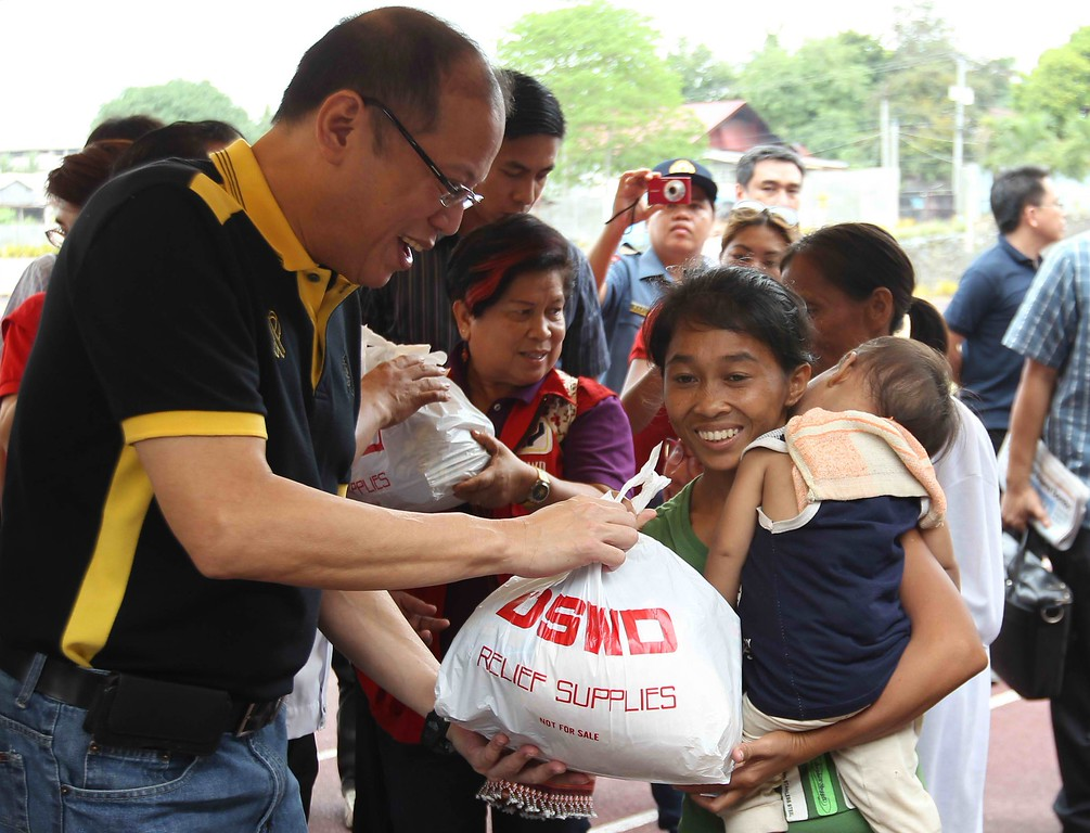 . In this handout photograph released by the Malacanang Photo Bureau, Philippine President Benigno Aquino (L) distributes relief goods to earthquake-affected families at Tagbilaran City, Bohol, central Philippines, on October 16, 2013. Rescue workers raced on October 16 to reach isolated communities on a popular Philippine tourist island that was devastated by a huge earthquake, as aftershocks tormented survivors and the death toll climbed to 107.AFP PHOTO/RYAN LIM/MALACANANG PHOTO BUREAU/AFP/Getty Images