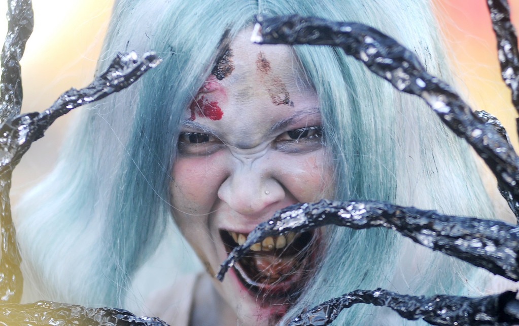 . Jessica Ward tries to scares crowd members during the annual Halloween parade on Thursday, Oct. 31, 2013, in Ashland, Ore. (AP Photo/The Medford Mail Tribune, Julia Moore)