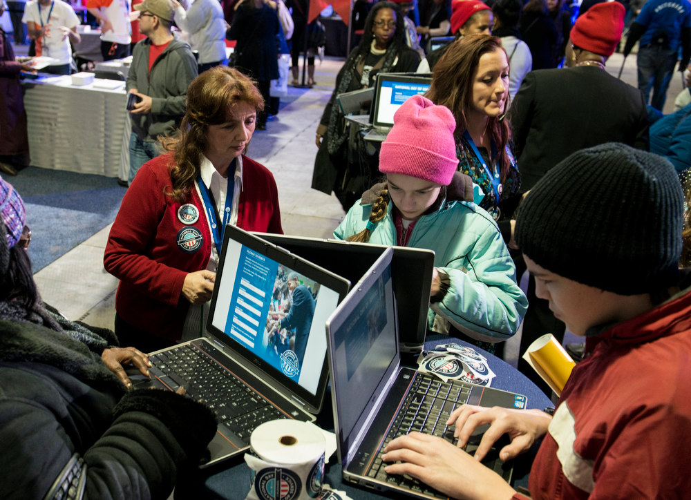 . People use computers during a service summit on the National Mall January 19, 2013 in Washington, DC. Events around the Inauguration started with a national day of service a yearly event where Americans are encouraged to volunteer and contribute to service projects to honor American civil rights leader Martin Luther King. BRENDAN SMIALOWSKI/AFP/Getty Images
