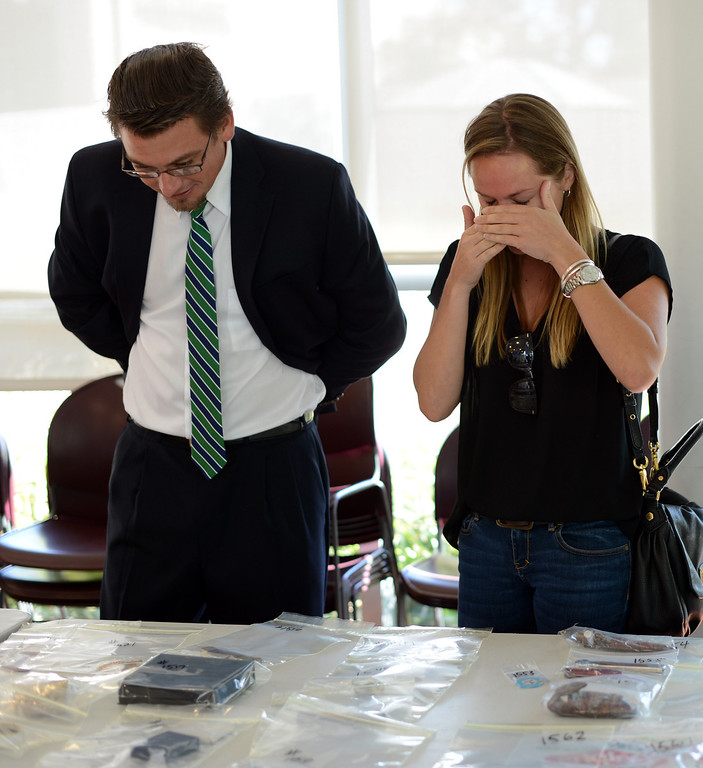 . Christina Carr wipes tears from her eyes as she and fiancé Dezi Reszneky find some of their property that was stolen during a public viewing of recovered stolen property at LAPD\'S Topanga Division in Canoga Park Thursday, September 26, 2013.  (Photo by Hans Gutknecht/Los Angeles Daily News)