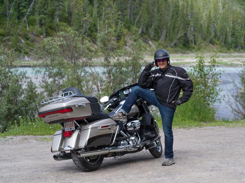 Man with his leg on a motorcycle, Saskatchewan River Crossing, Icefields Parkway, Jasper, Alberta, Canada
