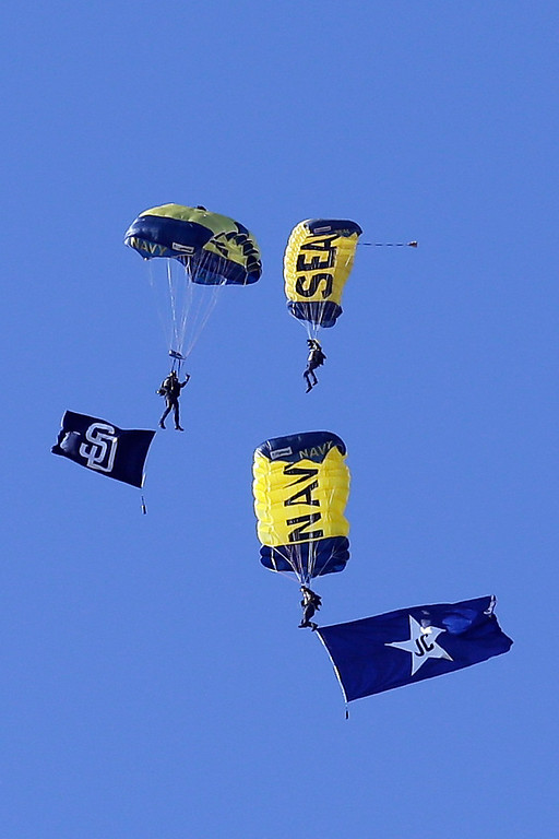 . The Navy SEAL Leapfrogs parachute over the stadium with a flag in honor of former San Diego Padres announcer Jerry Coleman before an opening night baseball game between the Los Angeles Dodgers and the Padres on Sunday, March 30, 2014, in San Diego. (AP Photo/Gregory Bull)